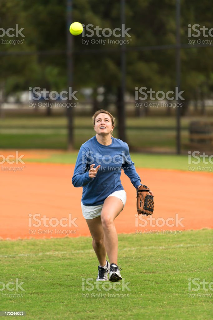 Young Woman Softball Player Running to Catch Ball royalty-free stock photo