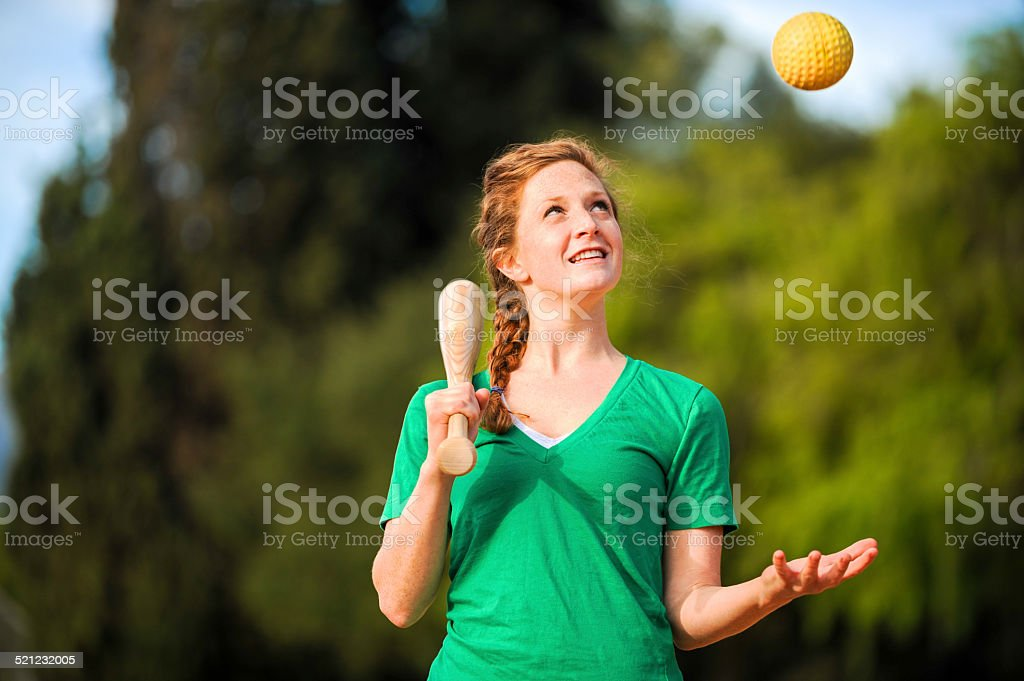 Young Woman Softball Player with Bat and Ball