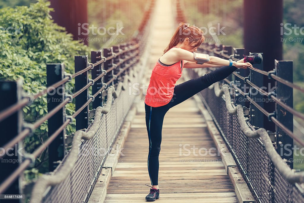 Young woman sports training at the rope bridge stock photo