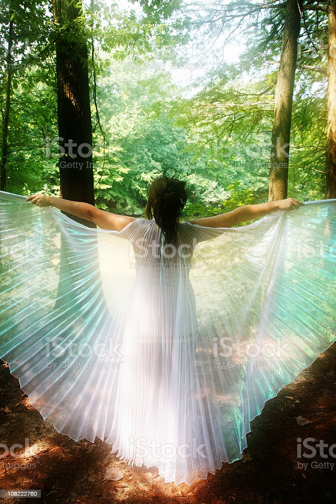 Young Woman Spreading White Wings in Forest stock photo