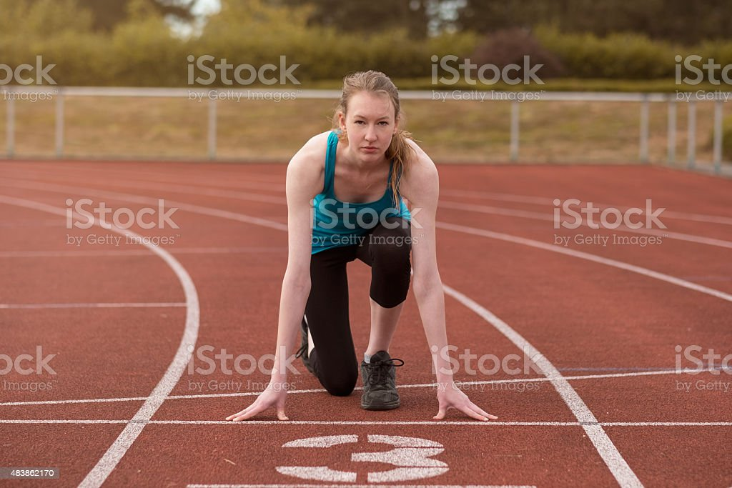 Young woman sprinter in the starter position stock photo