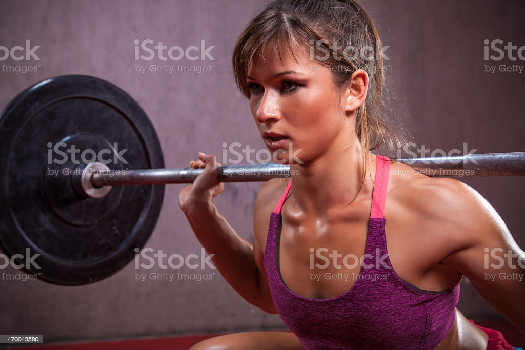 Young woman squatting with weights on shoulders stock photo