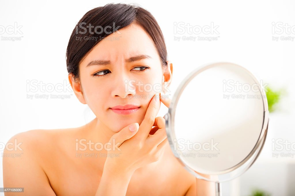 young woman Squeezing pimple looking on mirror stock photo