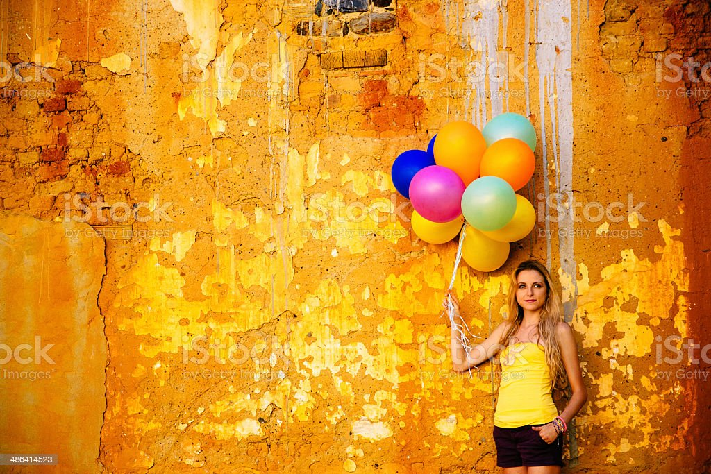 Young woman standing against old wall with balloons royalty-free stock photo