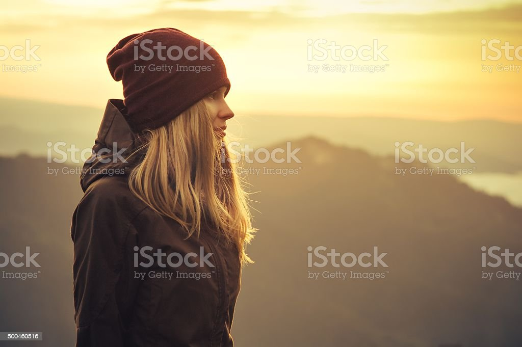 Young Woman standing alone outdoor with sunset mountains stock photo