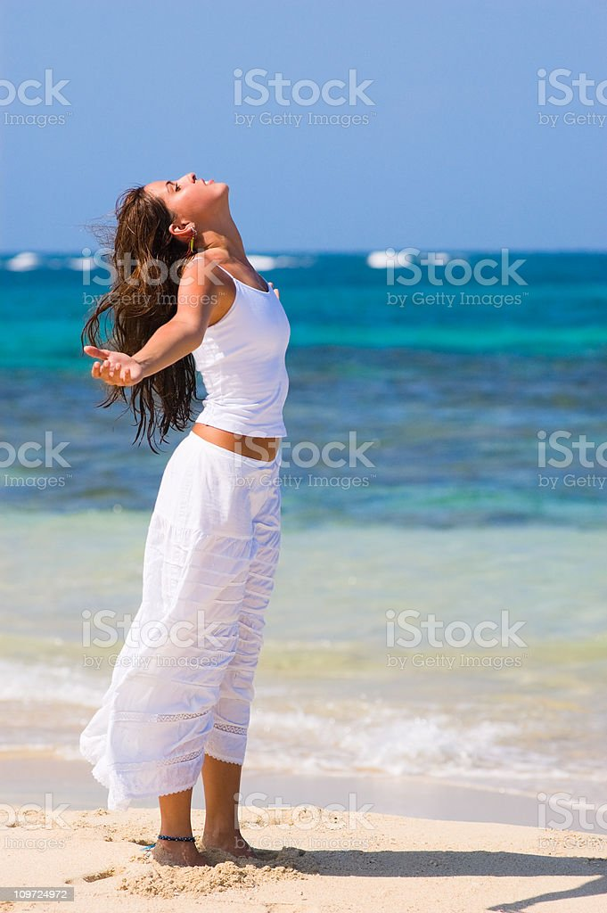 Young Woman Standing and Doing Relaxation Exercise on Beach royalty-free stock photo