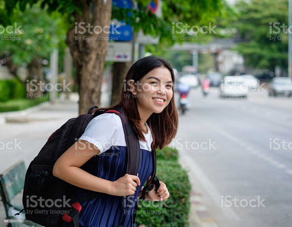 Young woman standing at a bus stop stock photo