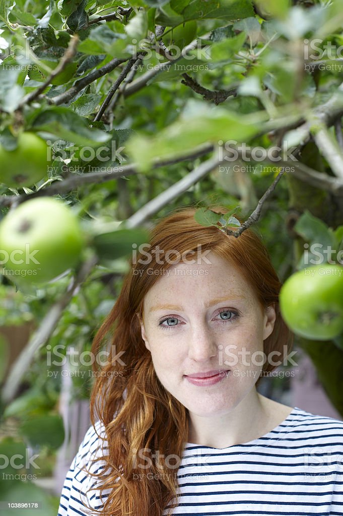 Young woman standing at apple tree royalty-free stock photo