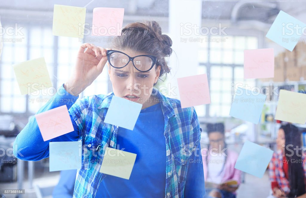 Young woman standing behind a glass wall with post-it notes stock photo