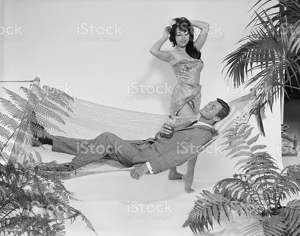 Young woman standing beside man relaxing in hammock with drink royalty-free stock photo