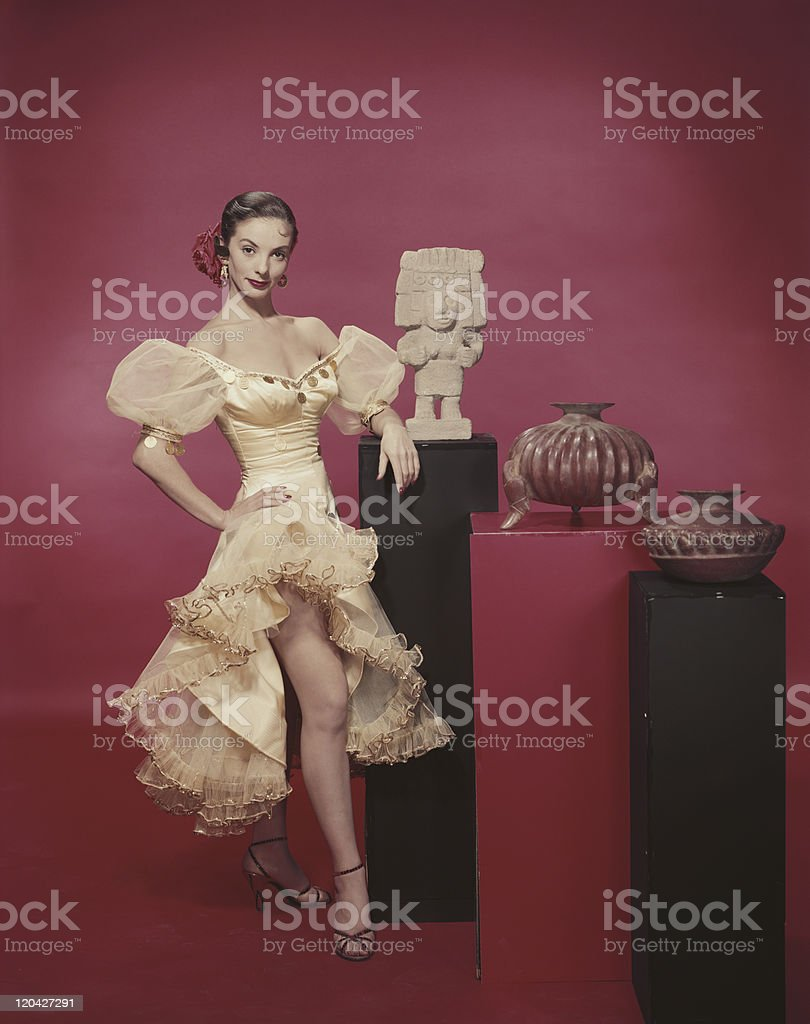 Young woman standing beside statue on red background, portrait royalty-free stock photo