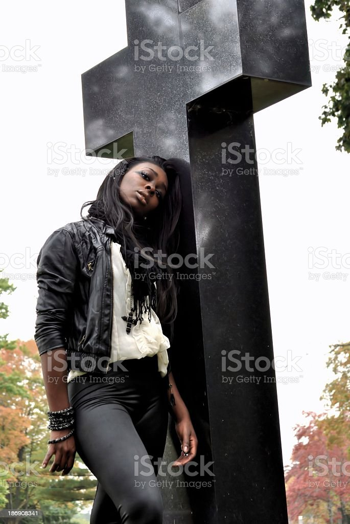 young woman standing by a cross royalty-free stock photo