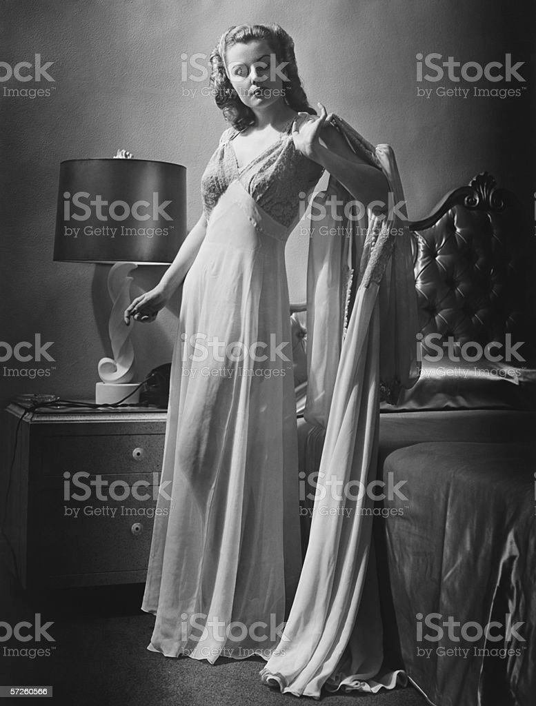 Young woman standing by bed wearing dressing gown, (B&W) stock photo