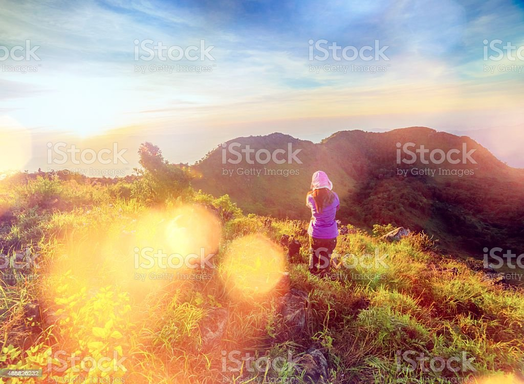 young woman standing during sunset stock photo