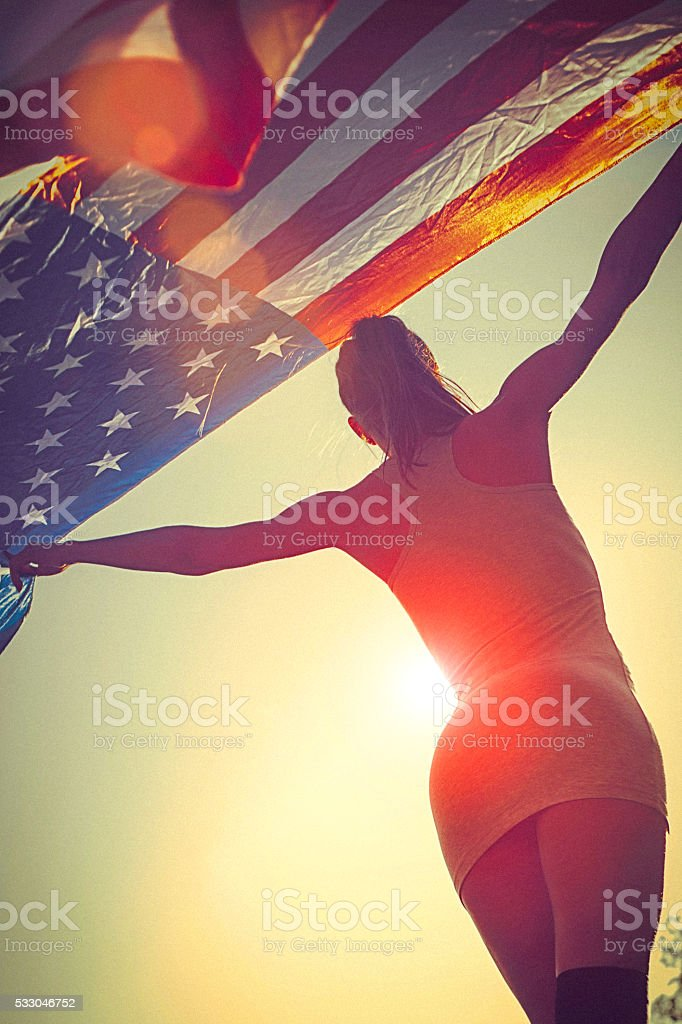 Young woman standing in a meadow holding american flag stock photo