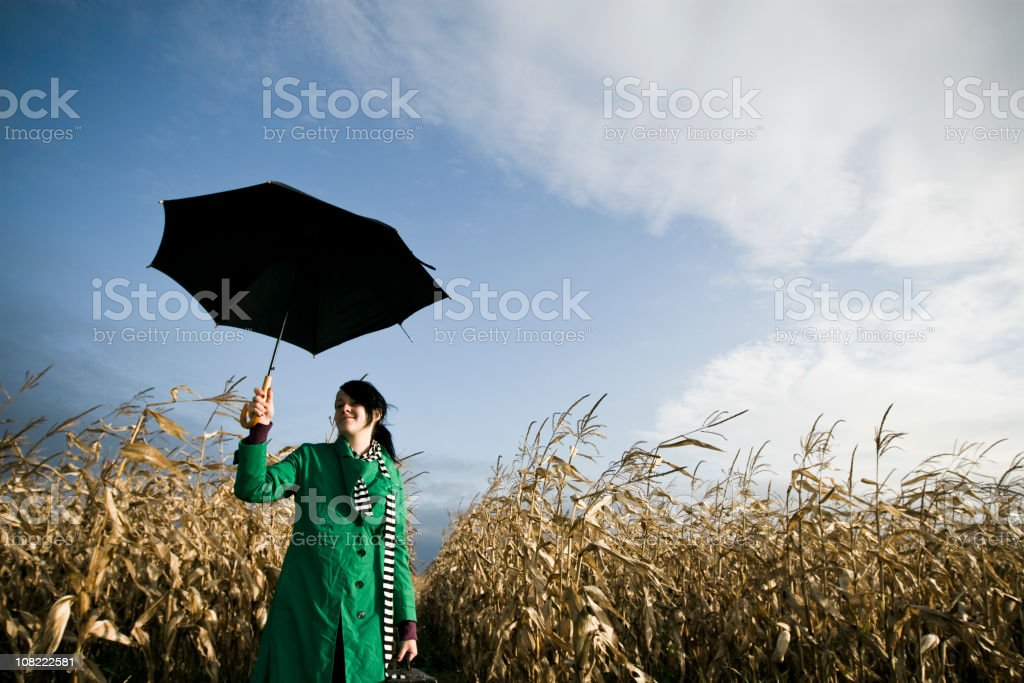 Young Woman Standing in Corn Field Holding Umbrella stock photo