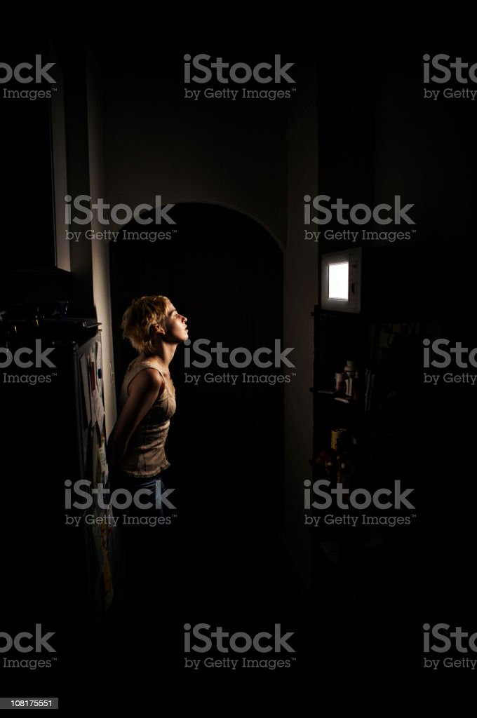 Young Woman Standing in Dark Waiting for Microwave to Finish stock photo