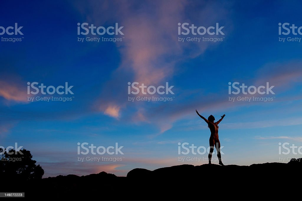 Young woman standing in desert with arms open, silhouette stock photo