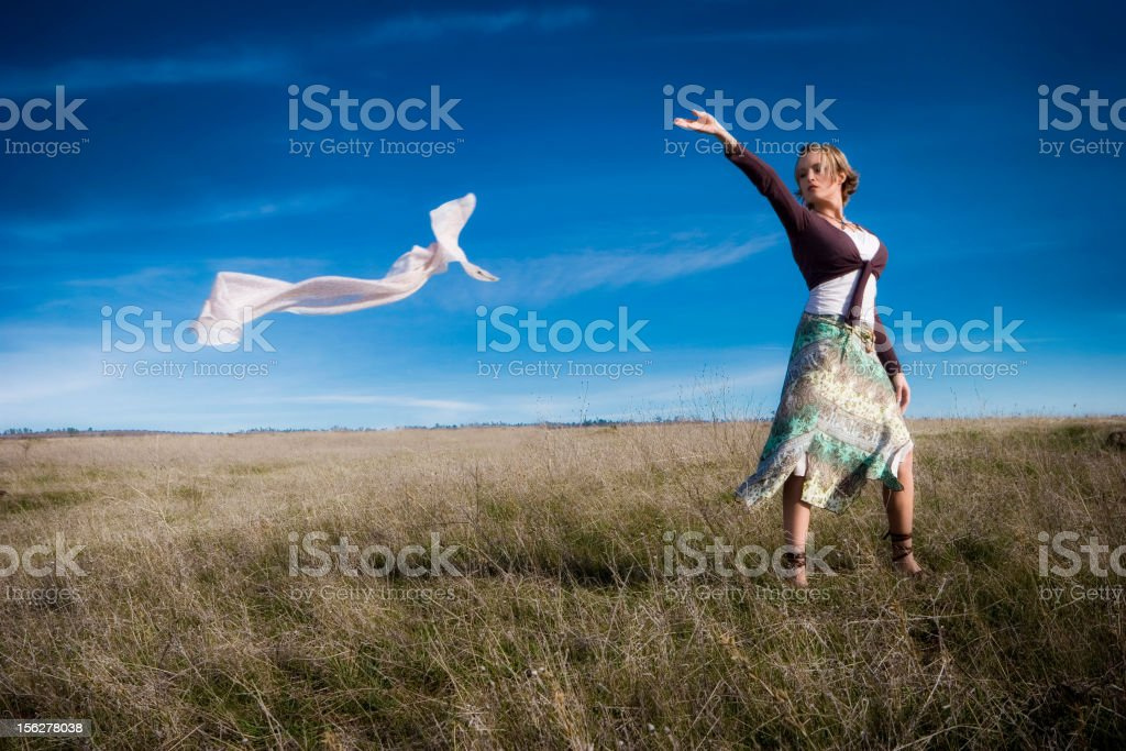 Young Woman Standing in Field Lettting Wind Take Scarf stock photo
