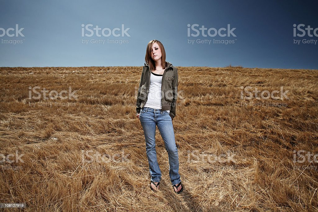 Young Woman Standing in Field royalty-free stock photo