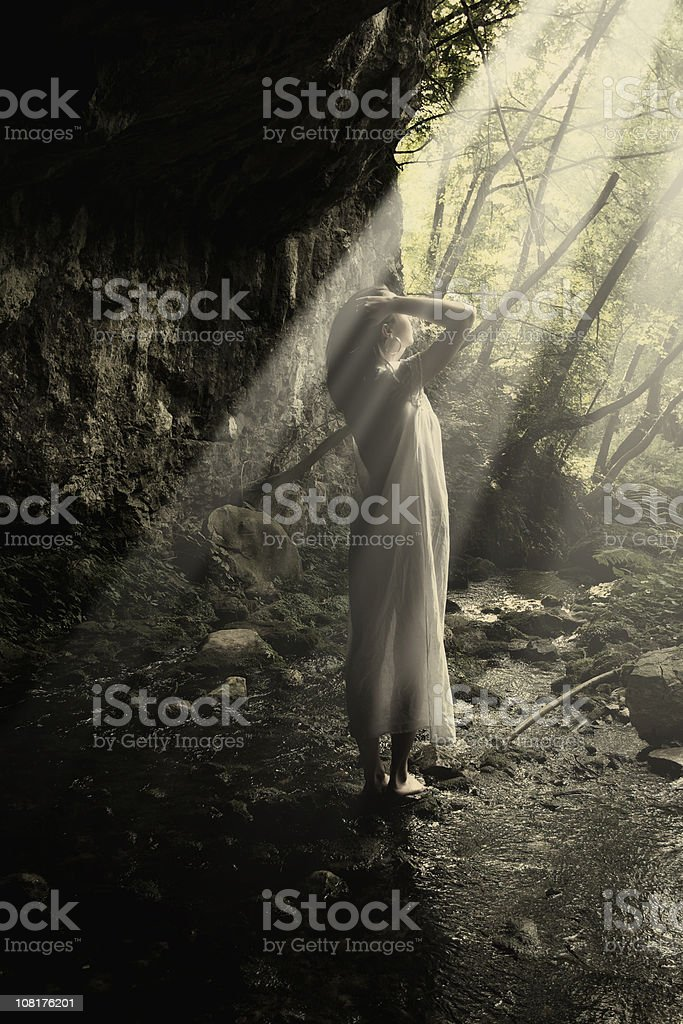 Young Woman Standing in Forest With Sun Light Shining royalty-free stock photo