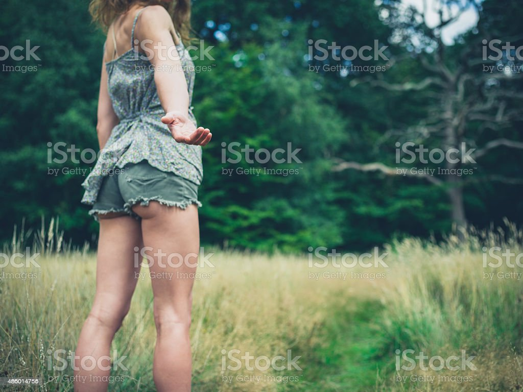 Young woman standing in meadow offering hand stock photo
