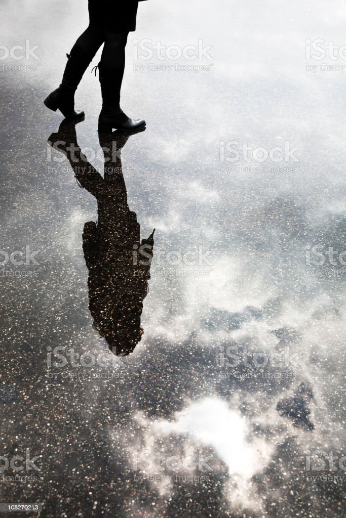 Young Woman Standing in Puddle with Reflection of Sky. royalty-free stock photo