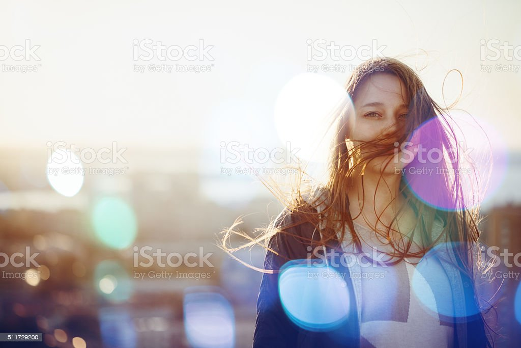 Young Woman Standing in Sunset Light stock photo