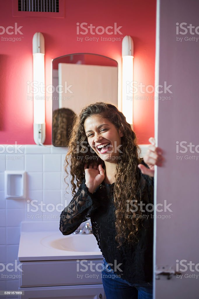 Young woman standing in the bathroom, laughing stock photo
