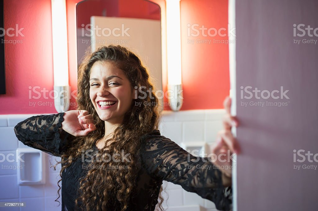 Young woman standing in the bathroom, smiling stock photo