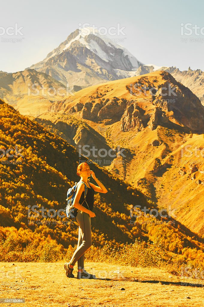 Young woman standing in the Caucasus mountains. stock photo