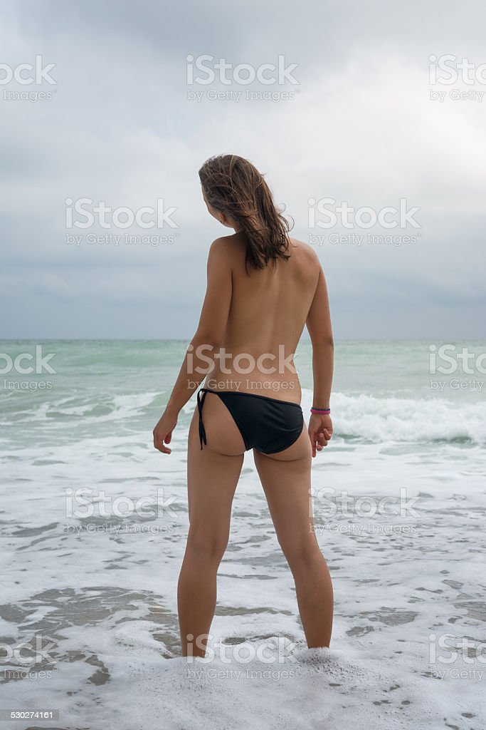 young woman standing in the waves stock photo