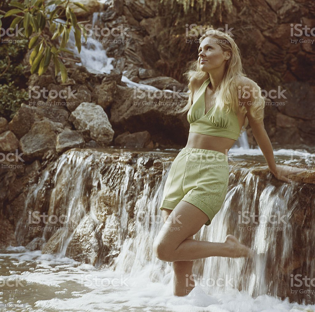 Young woman standing in waterfall stock photo