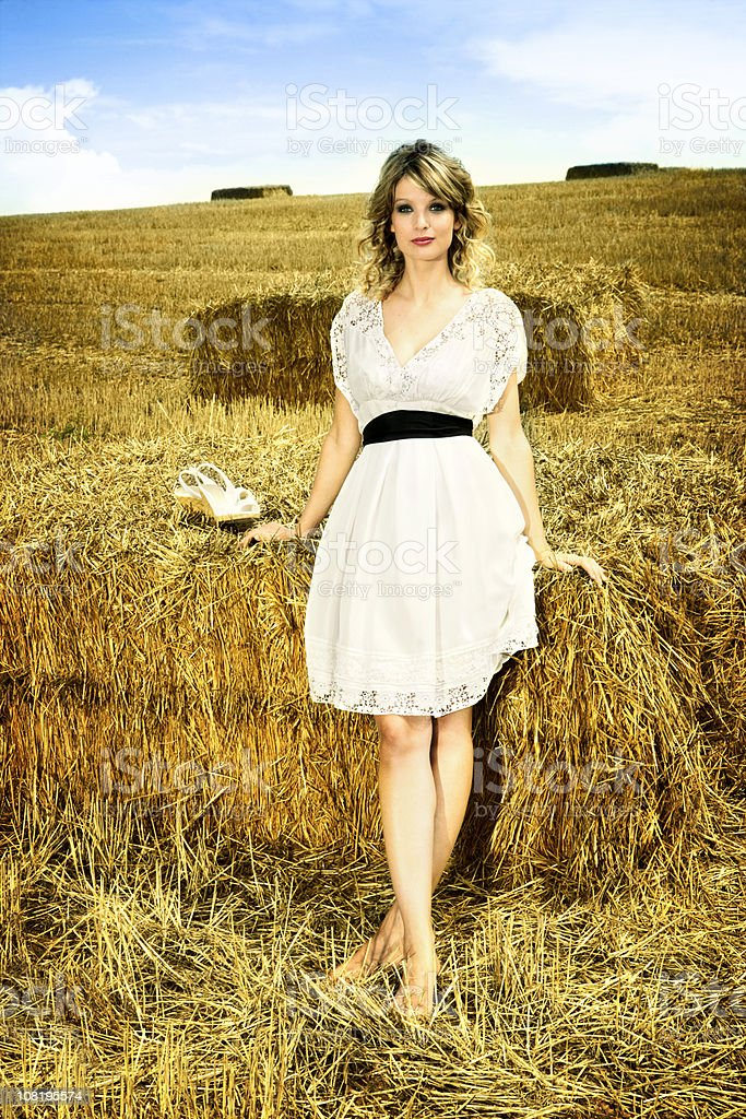 Young Woman Standing in Wheat Field By Hay Bales royalty-free stock photo