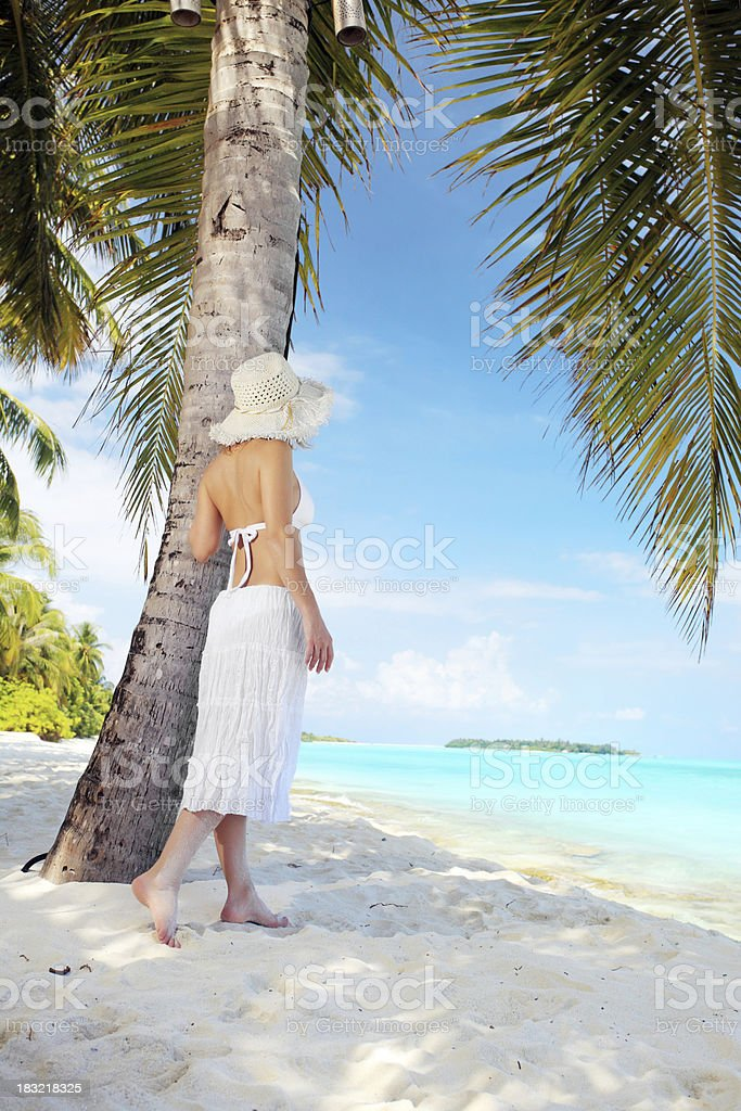Young woman standing near palm on the Maldivian beach royalty-free stock photo