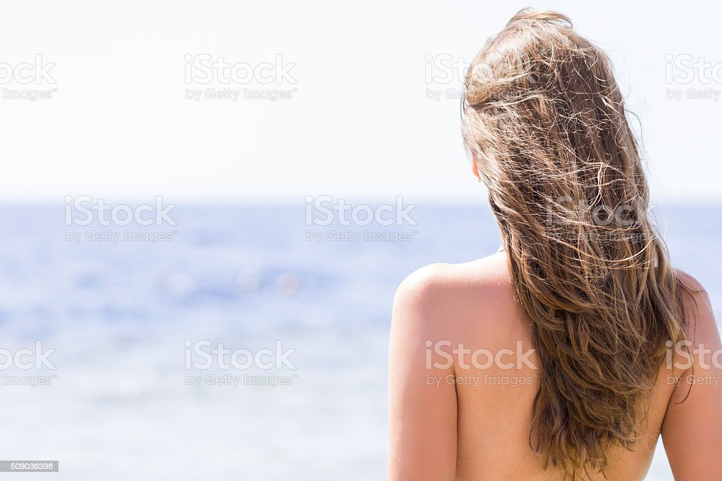 Young woman standing near the sea stock photo