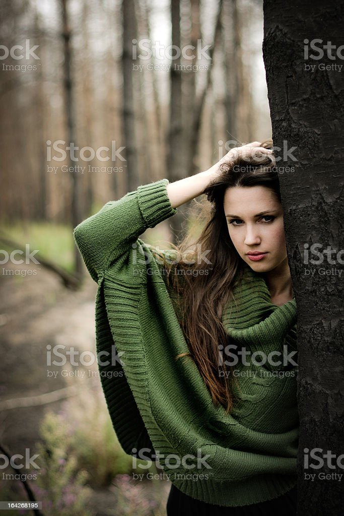 Young woman standing near tree stock photo