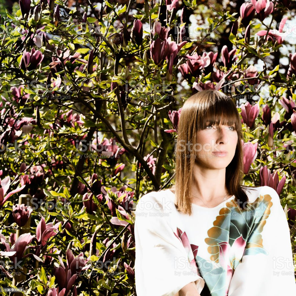 Young Woman Standing Near Tree with Flowers royalty-free stock photo