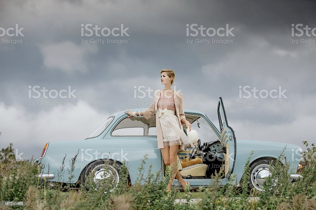 Young woman standing next to a vintage car stock photo