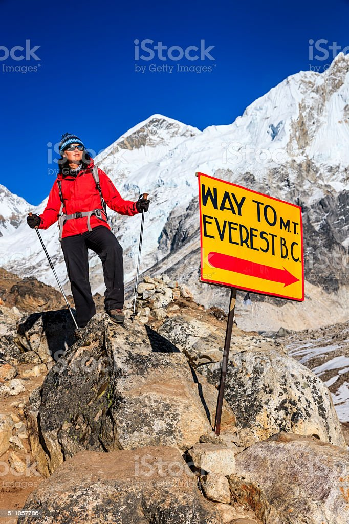 Young woman standing next to signpost 'Way to MountEverest BaseCamp' stock photo