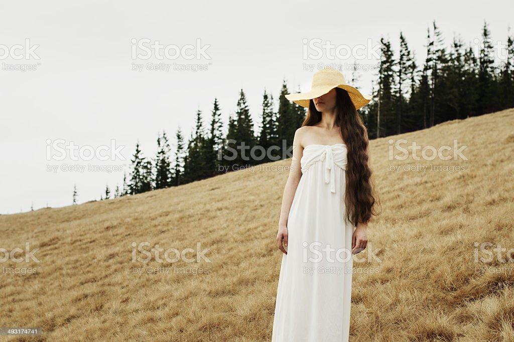 Jeune femme debout sur le bord d'une colline dans des montagnes photo libre de droits