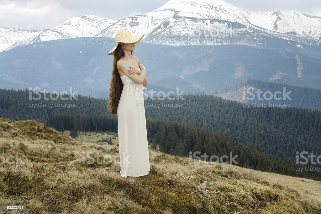Young woman standing on a hillside in the mountains stock photo