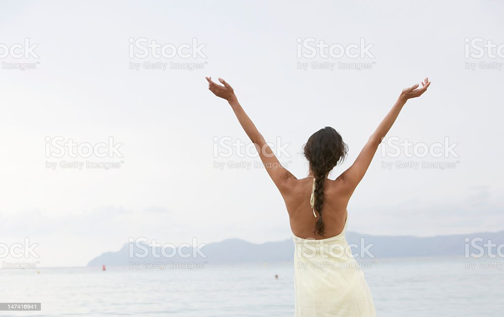 Young woman standing on beach, arms raised, rear view stock photo