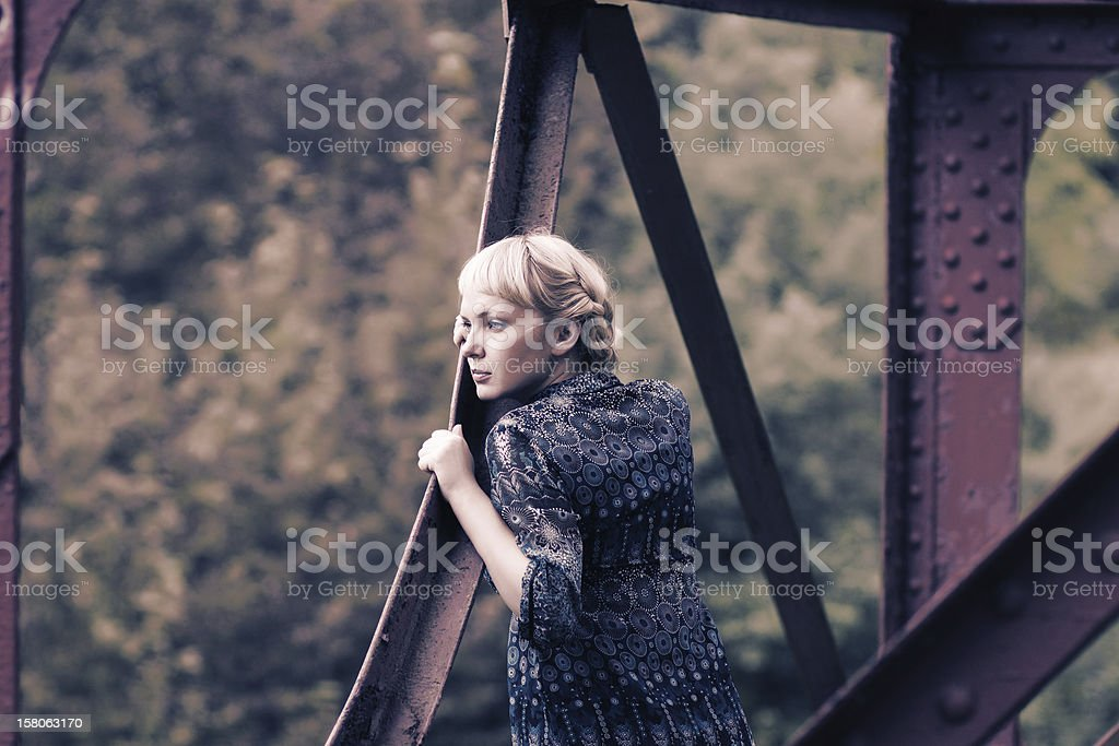 young woman standing on bridge bearing royalty-free stock photo