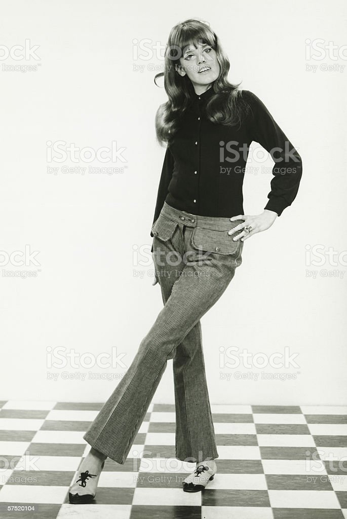 Young woman standing on checked floor, (B&W) royalty-free stock photo