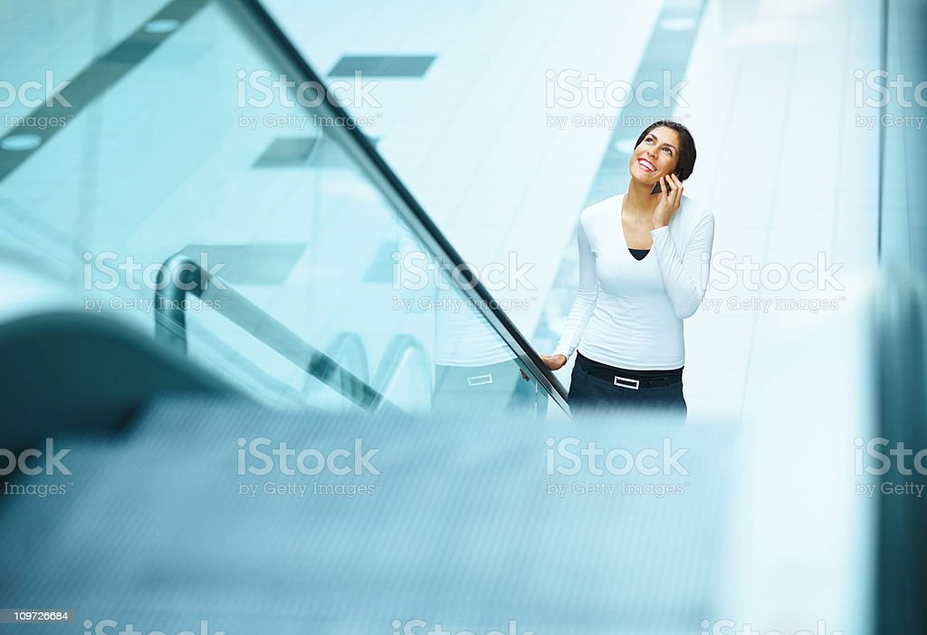 Young woman standing on escalator and using cellphone royalty-free stock photo