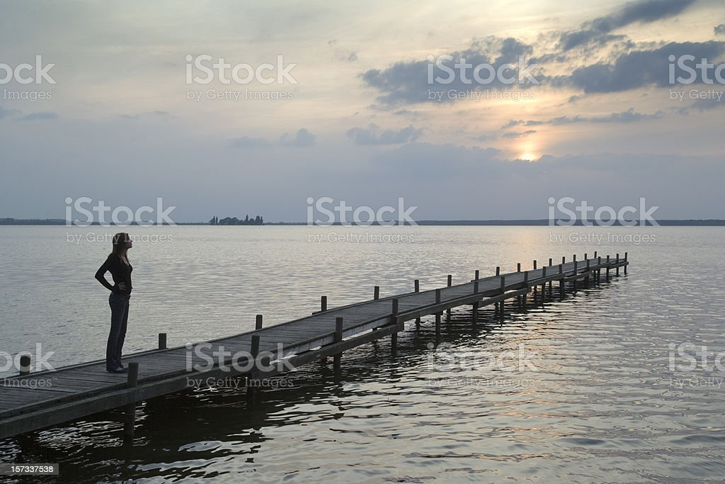 Young woman standing on lakeside jetty watching sunset (XXL) royalty-free stock photo