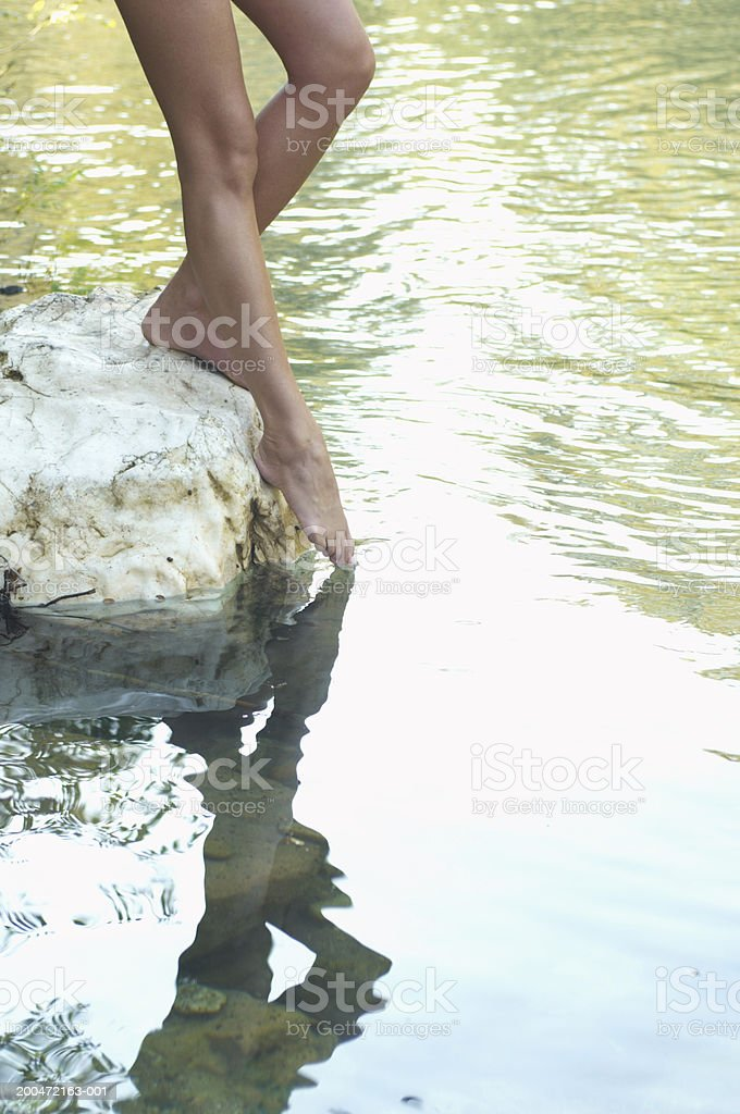 Young woman standing on rock, dipping toes in river,  low section stock photo