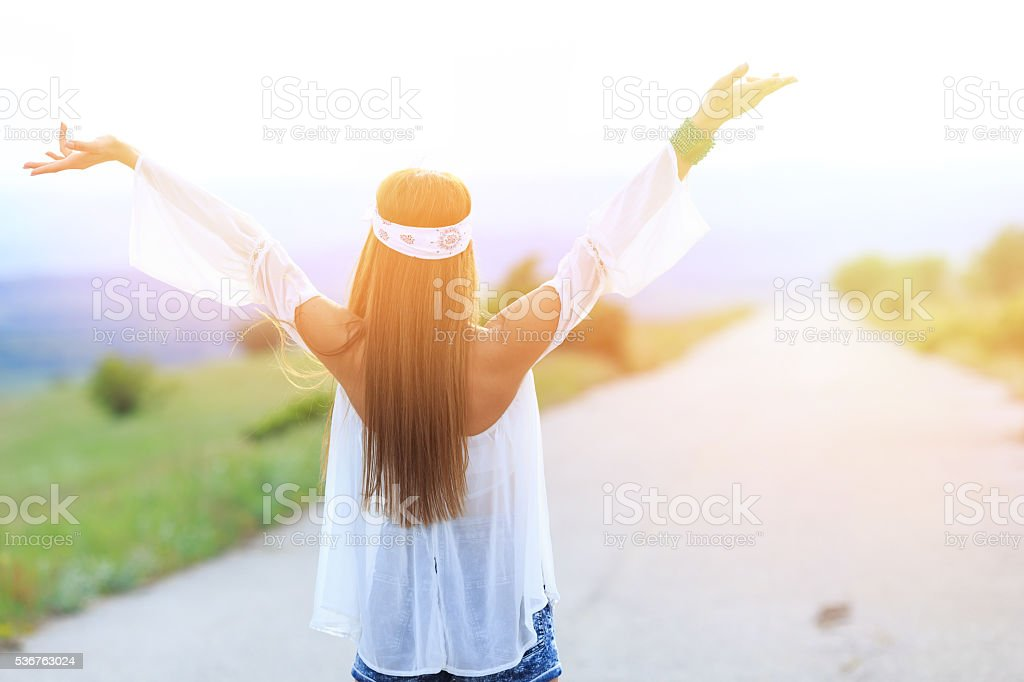 Young woman standing on the road hands raised stock photo