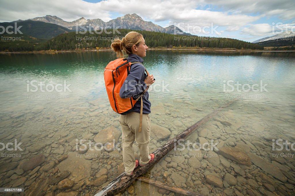 Young woman standing on tree log above lake stock photo